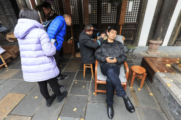 Chengdu, China - December 9, 2018: Group of people watching a chinese man getting his ear wax removed, a common and popular practice in Chengdu Ear Wax Chengdu Sichuan China ASIA Cerumen Cleaning Beauty Kuan-zhai Lane Chinese Medicine Full Length Group Of People