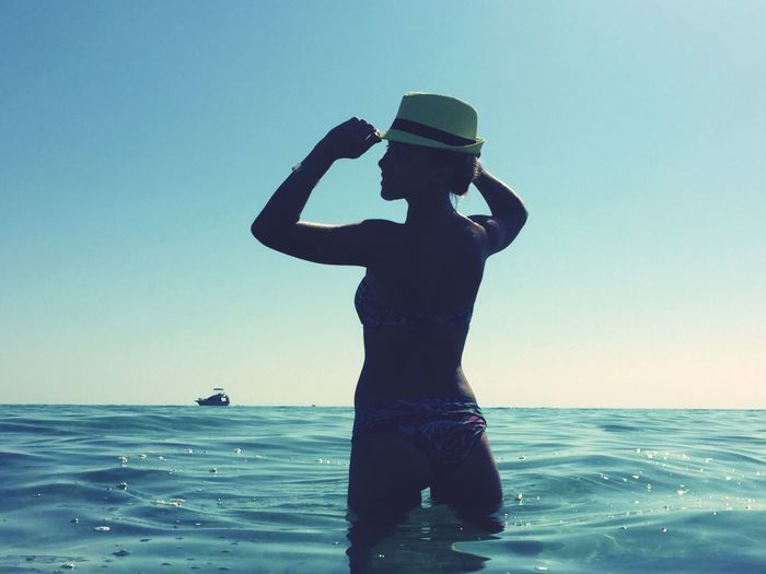 Full length of woman standing in sea against clear sky