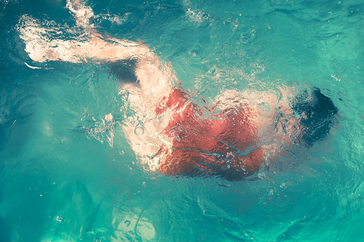 Full length of woman swimming in blue sea
