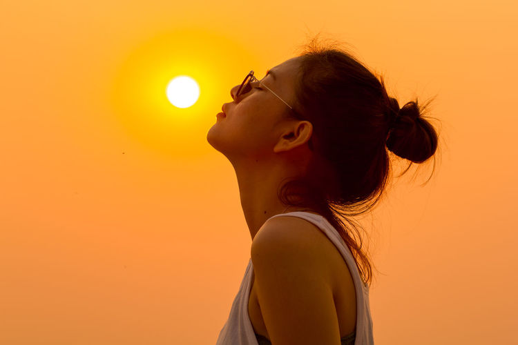 Woman with closed eyes against clear orange sky during sunset