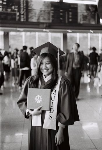 Portrait Of Smiling Woman In Graduation Gown Holding Diploma While Standing In College