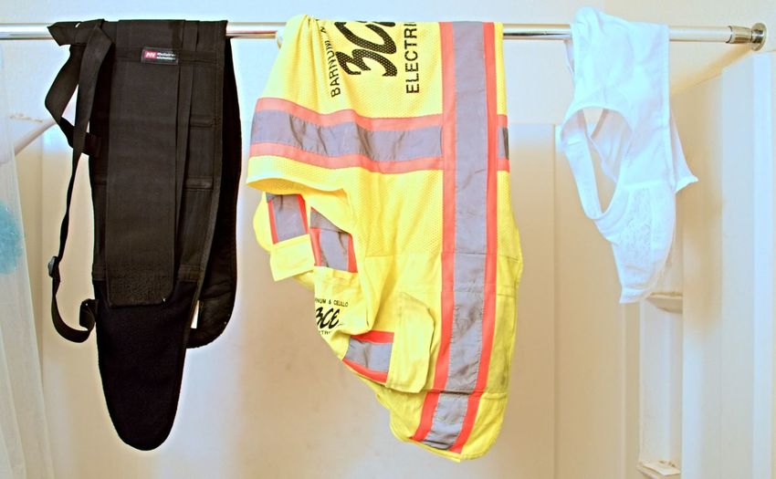 Juxtaposition of Masculine and Feminine .  Three items, recently washed, hanging on the Shower Curtain Rod to dry:  My Back Support Belt and High Visibility Safety Vest—which I wear as a big, Tough, Macho Construction Worker, next to my Wife's Pretty, Delicate, Lace Brassiere.     Bra Pretty Bra Lace Bra