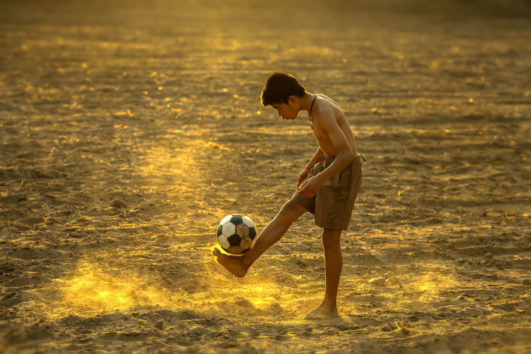Side View Of Boy Playing With Ball At Sunset