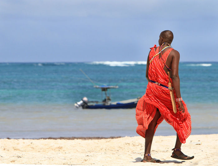 Rear view of masai man walking at beach