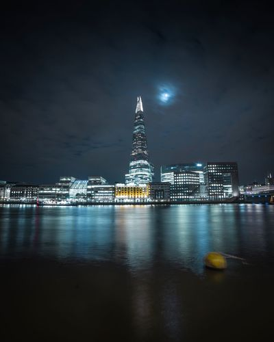 Illuminated Shard In City By Thames River Against Sky At Night