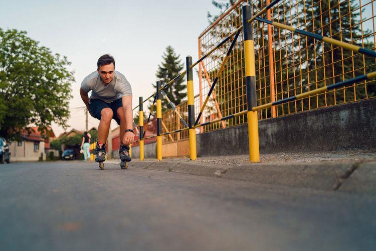 Full length of man roller skating on road