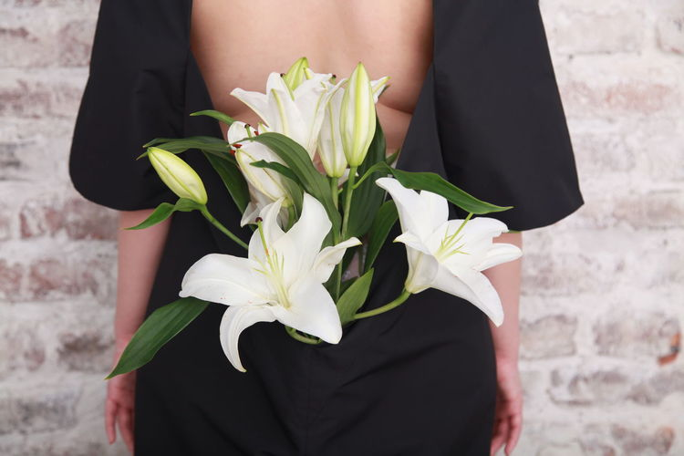 Fashion details, bouquet of white lilies is hidden in the dress of a girl, who is standing backwards