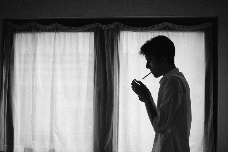 a young man lightning up a cigarette Adult Cigar Communication Curtain Holding Home Interior Indoors  Lifestyles Men Mobile Phone One Person Profile View Real People Shillouette Side View Standing Telephone Using Phone Waist Up Window Young Adult Young Men