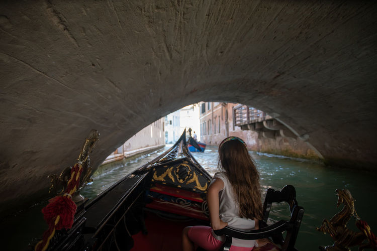 Little girl on board of a gondola under a bridge on a narrow canal in Venice, Italy Transportation Water Nautical Vessel Real People Leisure Activity One Person Architecture Lifestyles Mode Of Transportation Rear View Built Structure Long Hair Sitting Arch Bridge - Man Made Structure Outdoors Canal Gondola Venice Italy Travel Tourism Tourist Destination Under A Bridge Famous Destination
