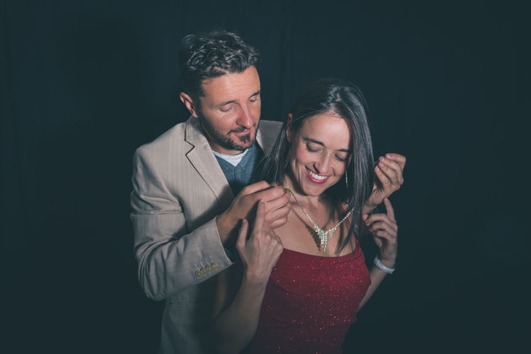 Man wearing necklace to woman against black background