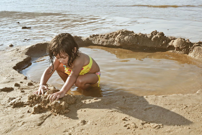Baby girl playing with water and sand on the beach Beach Boys Childhood Day Digging Elementary Age Full Length High Angle View Leisure Activity Nature One Person Outdoors Real People Sand Sand Pail And Shovel Sea Shirtless Vacations Water Wet