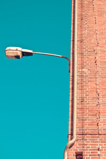 Architecture Blue Blue Wave Brick Brick Wall Building Building Exterior Built Structure Clear Sky Composition Day Electricity  High Section Lamp Low Angle View No People Outdoors Sky Tall - High Wall Wall - Building Feature