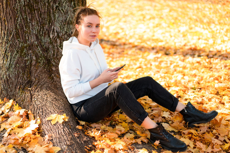 Young woman using mobile phone while sitting on sidewalk