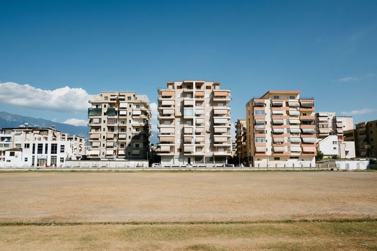 Buildings on field against blue sky