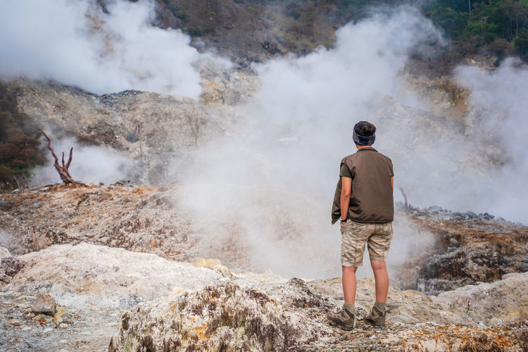 Rear view of man standing on volcanic landscape