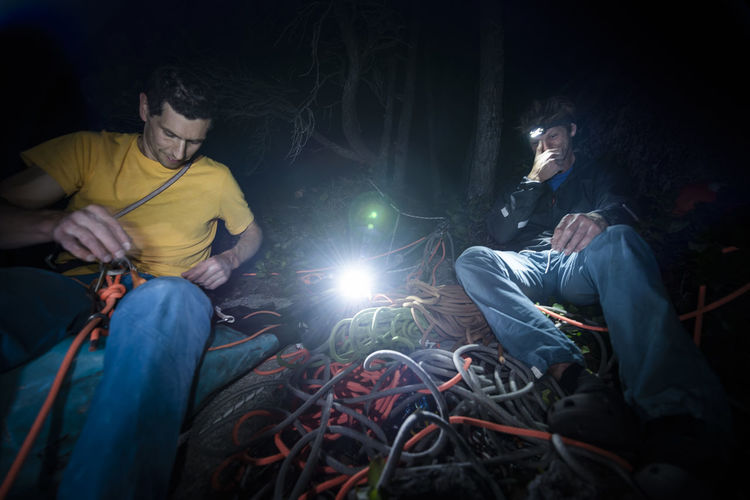 Midsection of man and woman sitting in illuminated lighting equipment