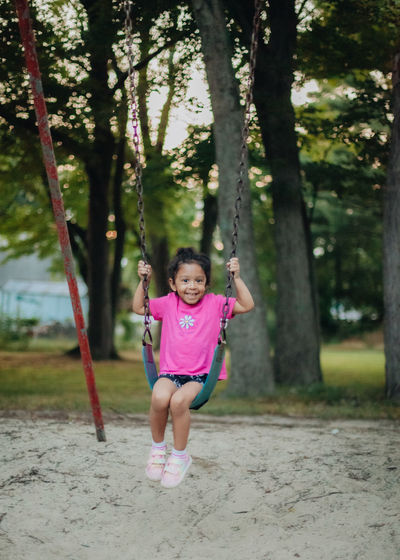 Portrait of cute girl sitting on swing at park