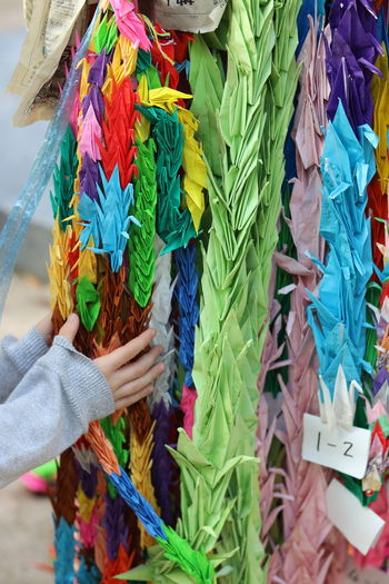 Cropped hands of child touching colorful decoration in market