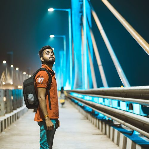 Side view of young man standing on footbridge in city at night