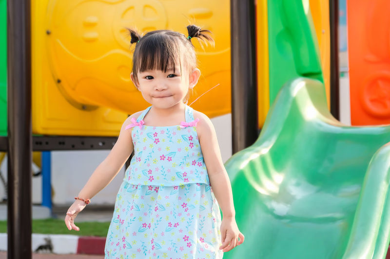 Portrait of cute baby girl standing at park