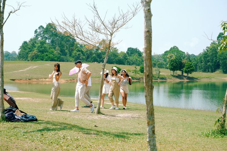 People standing by lake against trees