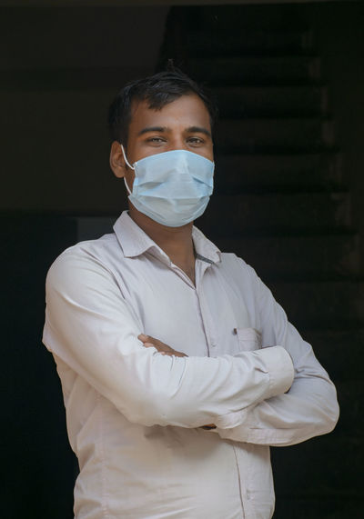 Portrait of young man wearing flu mask standing at home