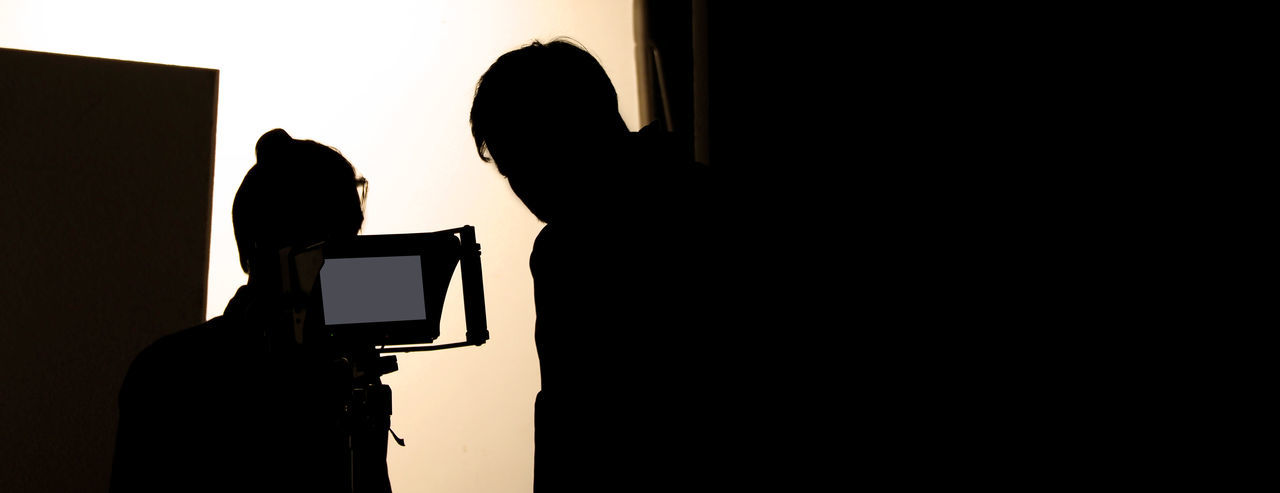Shooting studio behind the scenes in silhouette images which film crew team working for filming movie or video with professional lighting and equipment such as camera, tripod, soft box, monitor Silhouette Men Indoors  Two People Real People People Lifestyles Technology Leisure Activity Women Adult Copy Space Standing Headshot Wall - Building Feature Portrait Photography Themes Togetherness Dark Studio; Photo; Shoot; Photography; Photographer; Equipment; Film; Model; Fashion; Professional; Behind; Shooting; Background; Camera; Photoshoot; People; Tv; Production; Lighting; Product; Scenes; Set; Woman; Light; Video; Black; Movie; Photograph; Scene;