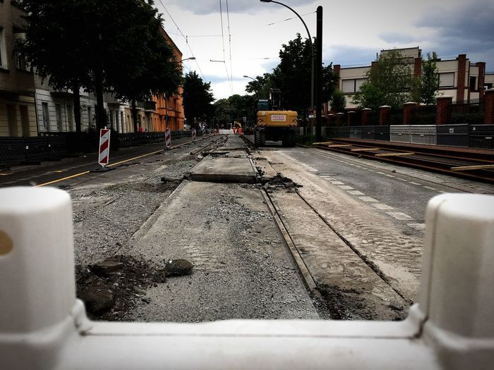 Surface level of railroad tracks in city against sky