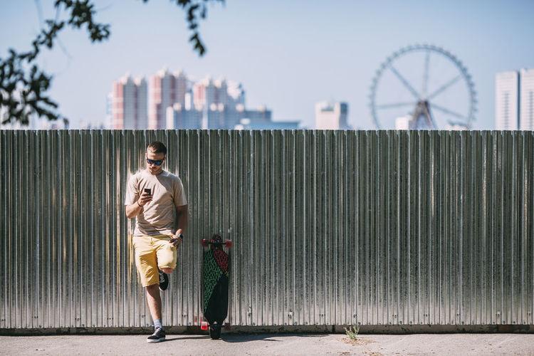 Man walking on bridge against sky in city