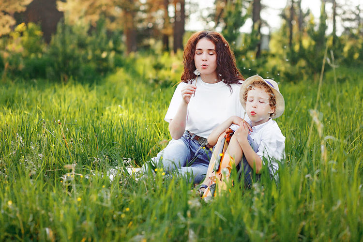 Full length of attractive curly woman and curly boy sitting  on grass