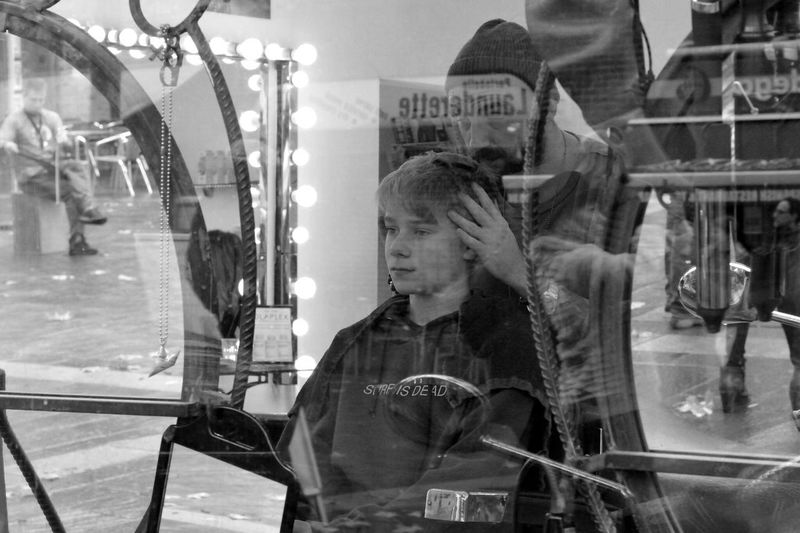 Reflection of young woman on mirror at store