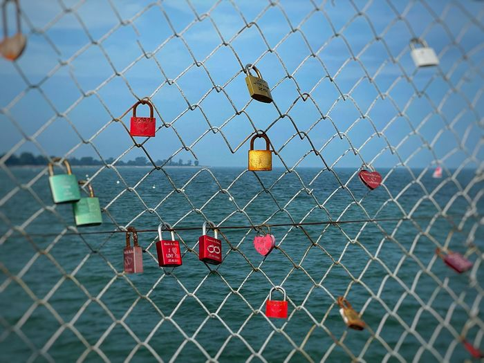 Red padlocks hanging on chainlink fence against sky