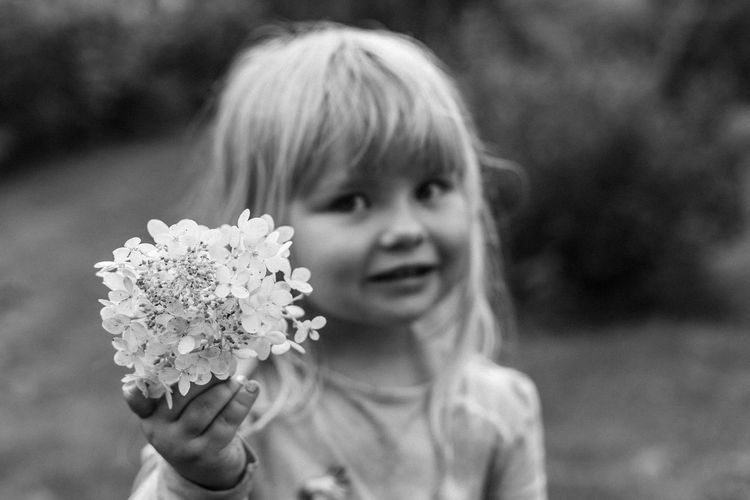 Close-up portrait of cute girl holding flower