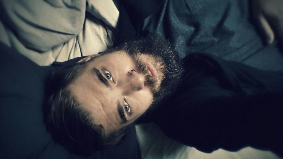 Directly Above Shot Of Bearded Man With Piercing Relaxing At Home