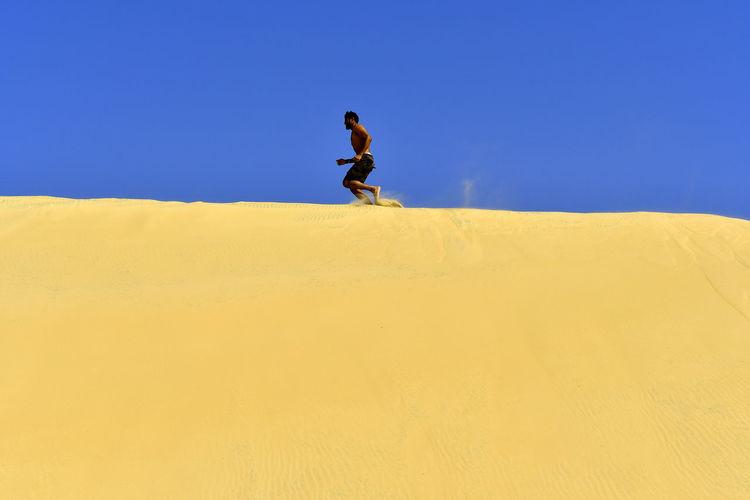 Man running on sand dune in desert against sky
