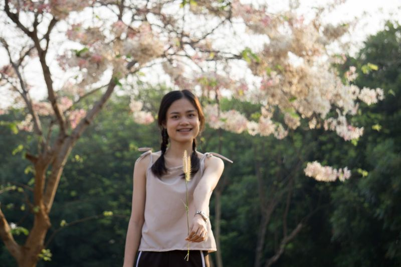 Woman with flowers. Thailand Sakura Lent Love Togetherness Get Flower Cherry Blossom Young Adult Tree Blossom Waist Up One Young Woman Only Young Women One Person Casual Clothing Toothy Smile Only Women Smiling Beauty Focus On Foreground Adult Springtime Outdoors Front View Nature