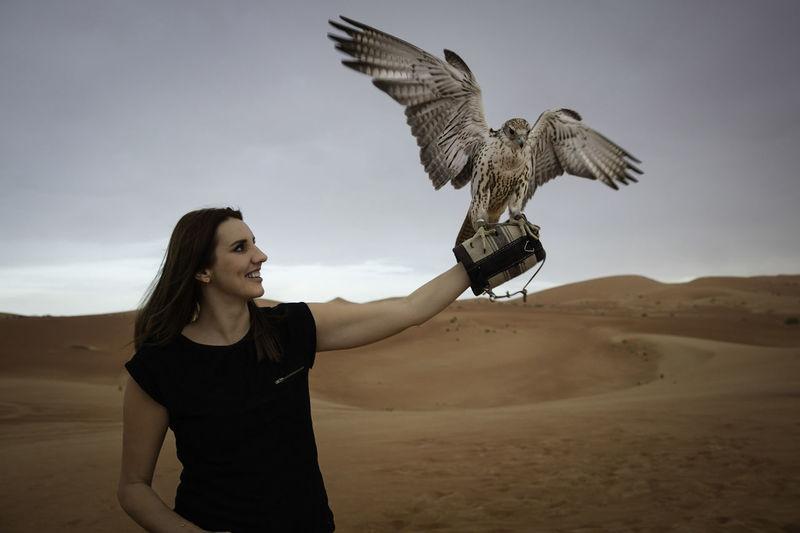 Woman flying bird on land against sky