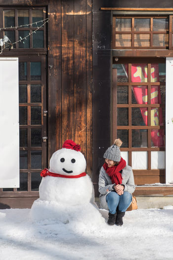 Woman Sitting By Snowman Against Closed Door