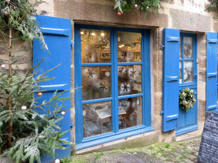 Magasin à l'approche des fêtes de fin d'année. Store at the approach of Christmas and New Year. Blue Branches Of Tree Brittany Building Exterior Christmas Decoration Crown Of The Avent Côtes D'Armor Decorated Window Decoration Dinan France No People Old Street Outdoors Shop Window