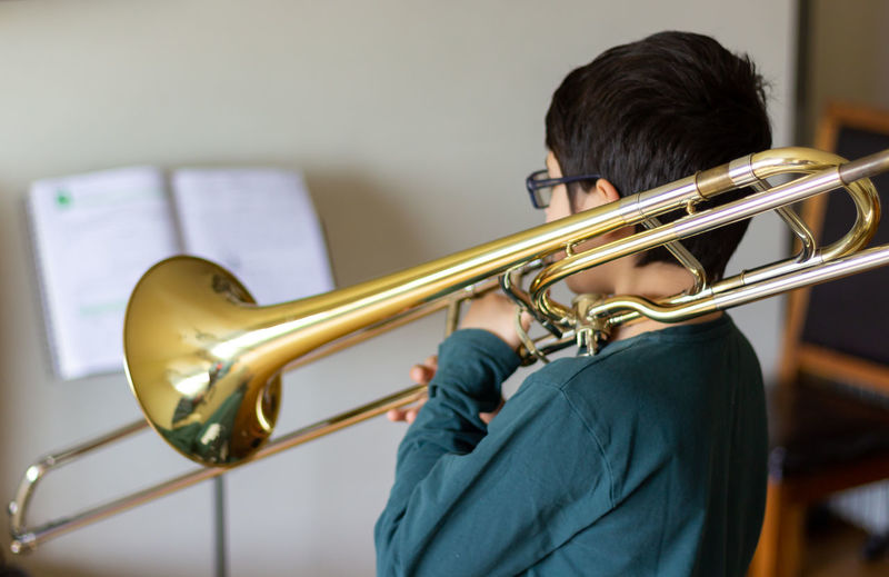 Boy Playing Trombone. Bronze Classic Glasses Jazz Lifestyle Sound Student Chidhood Child Concert Conservatory Holding Indor Metal Music Music Style  Musical Instrument Musician One Person Orchestra Sheet Music Solo Talent Trombone Wind Instrument