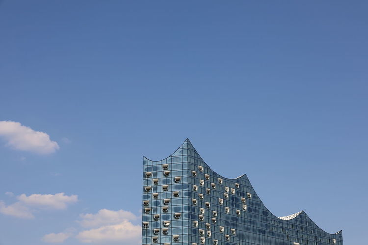 Low angle view of elbphilharmonie against blue sky in hamburg