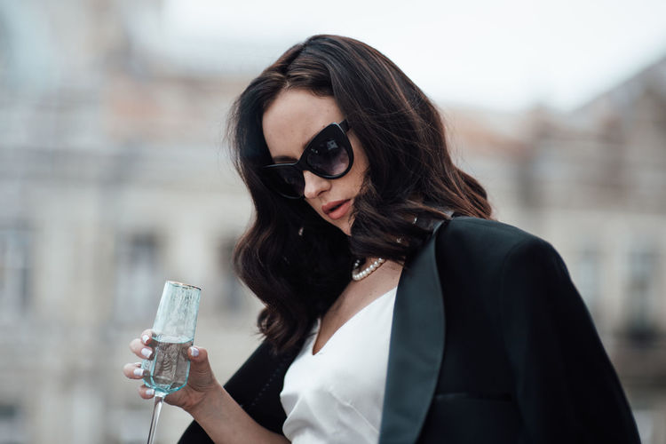 Portrait of woman with sunglasses standing outdoors