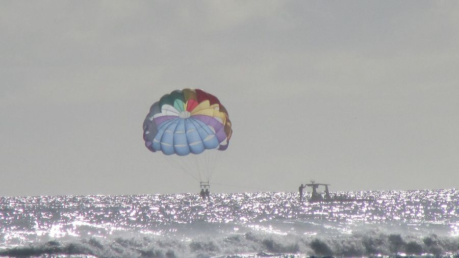 Distant view of people parasailing over sea
