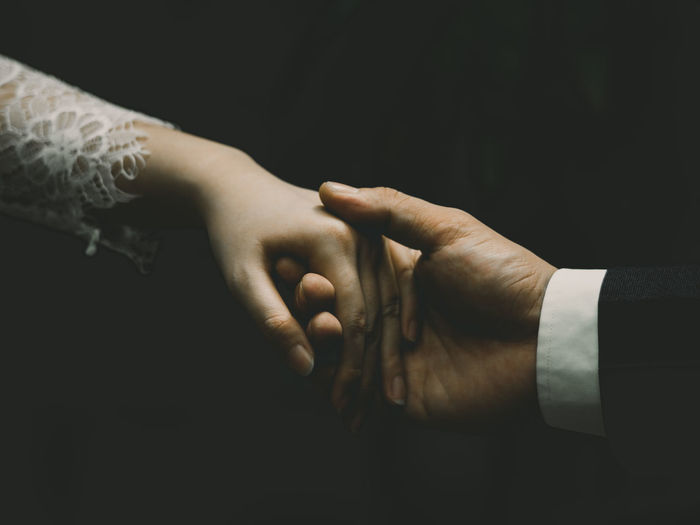 Close-Up Of Couple Holding Hands Over Black Background