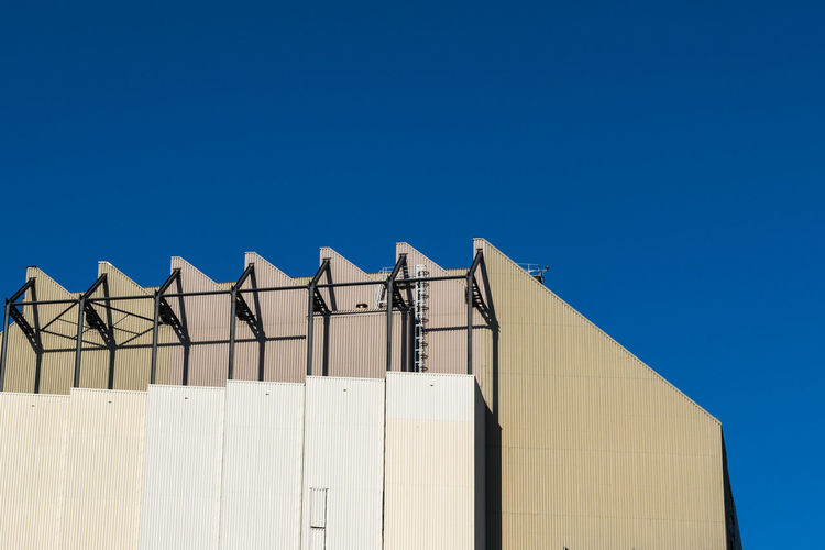 Low angle view of an industrial building against clear blue sky