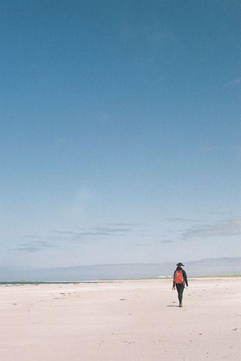 Woman Walking At Beach Against Blue Sky