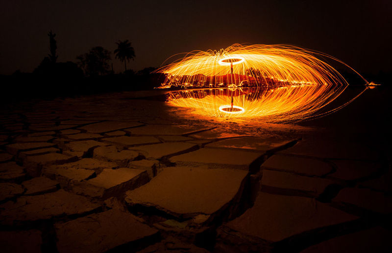 Steel Wool in Indonesia Night Illuminated Wire Wool Motion Long Exposure Nature Orange Color Glowing Sky Burning Fire Blurred Motion Spinning Water Land Beach Outdoors Shape No People Sparks