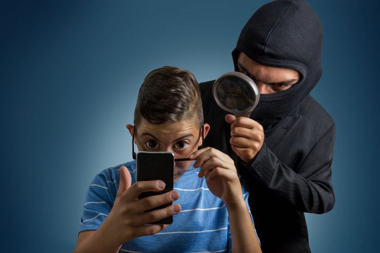 Detective Standing With Magnifying Glass Behind Boy Using Mobile Phone Against Blue Background