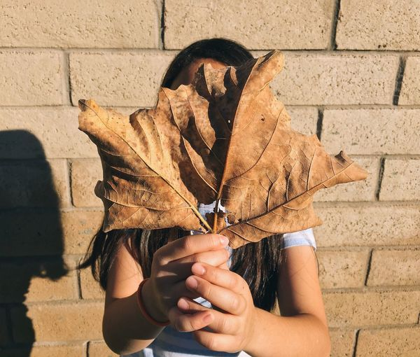Young Woman Hiding Face With Dry Leaves Against Brick Wall