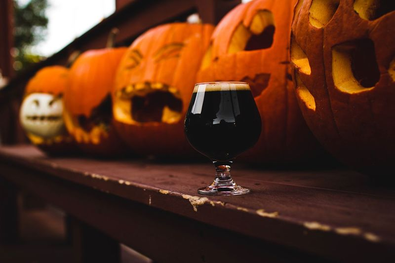 Close-Up Of Drink Against Jack O Lanterns On Table